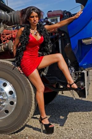 camión cisterna: Mujer sexy en vestido rojo recostado en un neumático de camión Foto de archivo