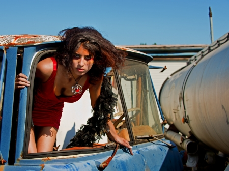 Hot woman in sexy red dress climbs through the truck windshield