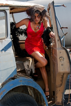Beautiful woman in sexy red dress exits a truck Stock Photo - 16966745