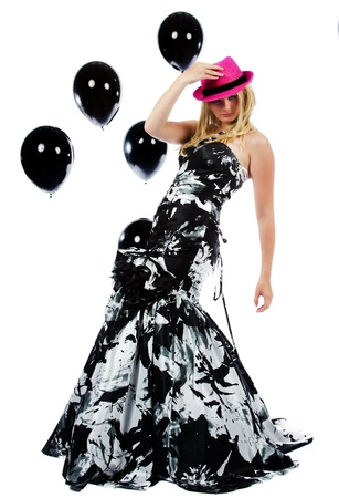 baloons: Beautiful teen gilr holding onto her hat as she dances the night away