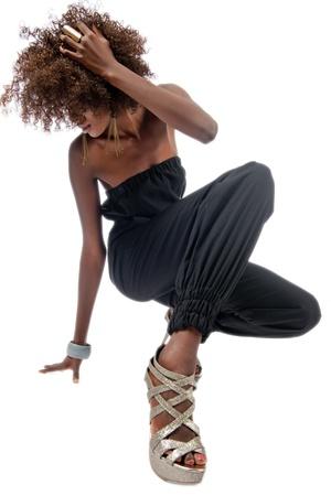 danza africana: Hermosa mujer de negro vestida a la moda en cuclillas