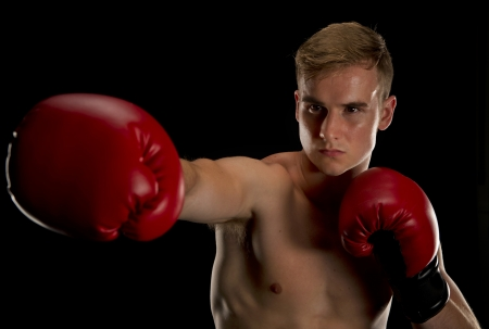 jab: Isolated on a black background a male boxer extends his right jab as he protects with his left