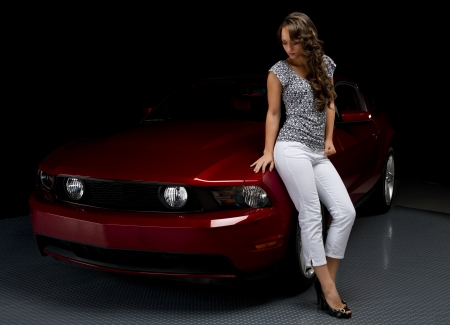 A beautiful young woman leans on the hood as she admires her red sports car in the shadows