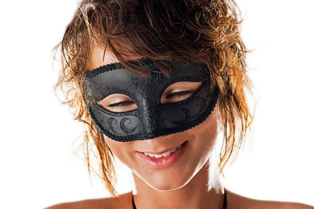 chuckles: A beautiful young woman with wet hair and an endearing smile behind the black mask she is wearing and isolated on a white background