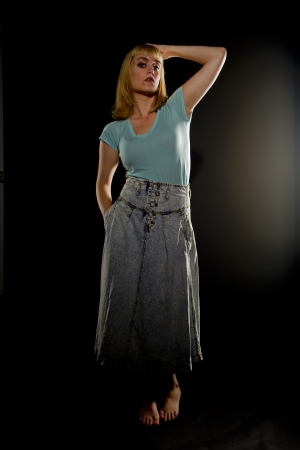 long skirt: Blonde woman in a long skirt plays with her hair as she emerges from the shadows