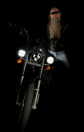 headlights: Biker in the dark shadows of the night Stock Photo