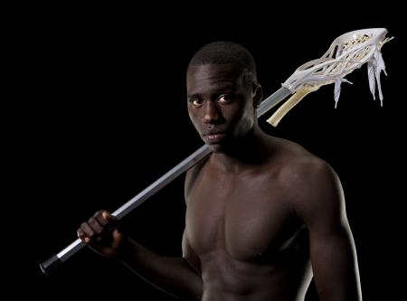 Athletic African American man with a lacrosse stick over his shoulder  Stock Photo - 16085398