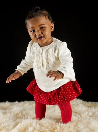 black sweater: Baby girl standing on a fur rug  Stock Photo