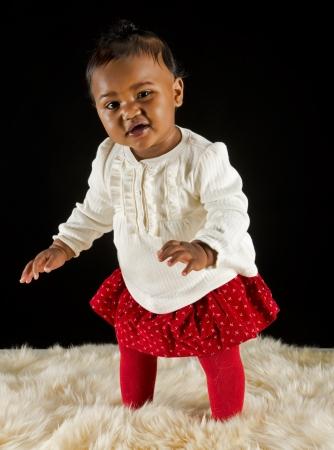 Baby meisje staande op een bont tapijt