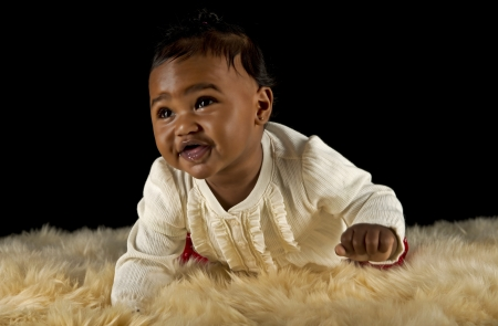 Baby girl crawling on a fur rug photo