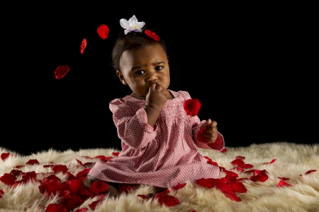Beautiful baby girl with rose pedals and fur rug photo