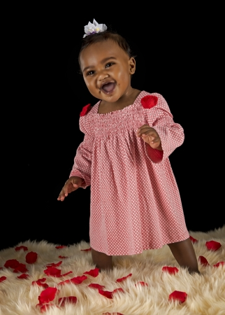 Black baby girl in pink dress with rose pedals photo