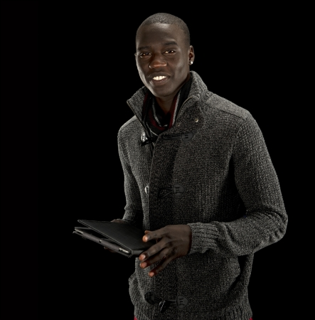 Black man with tablet PC smiles at the camera