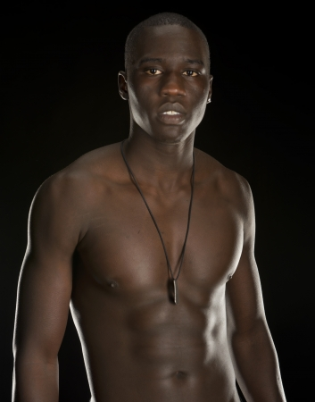 Bare chested young black male model isolated on a black background  Stock Photo