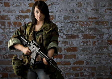 daughter in law: Young woman in military clothing holding an M16 in front of a distressed brick wall