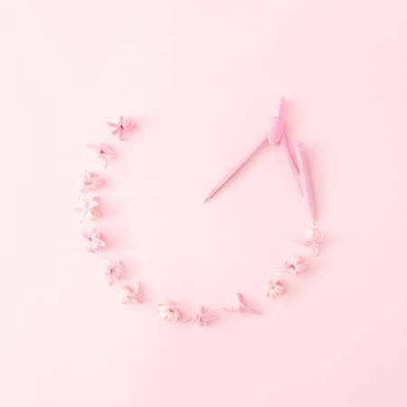 Round frame made of pastel pink hyacinth petals and drafting compass on pastel pink background. Minimal spring or summer concept. Flat lay.