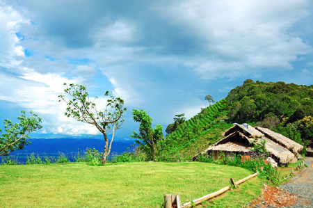 Bamboo hut in hill tribe village with cloud and blue sky , Chiang mai ,Thailand photo