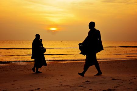 Silhouette of monk walk on the beach , Huahin , Thailand photo