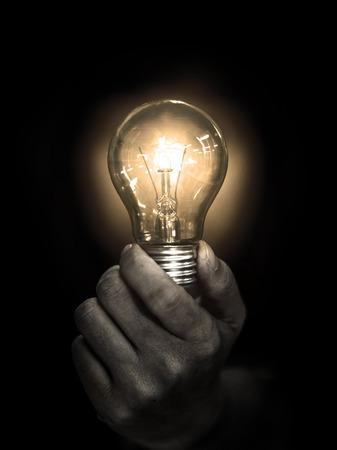 lightbulb hold in hand on black background