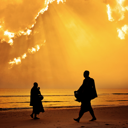 Silhouette of monk walk on the beach with beutuful , Huahin , Thailand photo