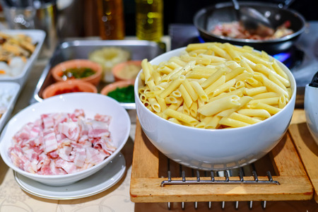 blow with different noodle dishes, both of which include meat and colorful garnishes photo