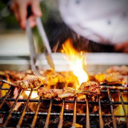 불꽃에 양고기 갈비를 굽고 요리사 스톡 콘텐츠