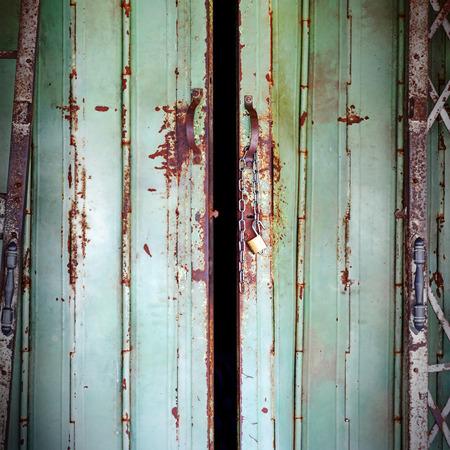 old rusty iron slide door with open lock photo