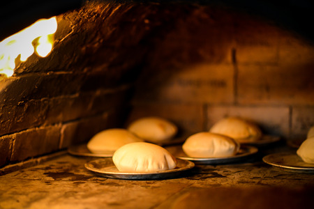 Stone wood oven with fire baking fresh homemade bread photo