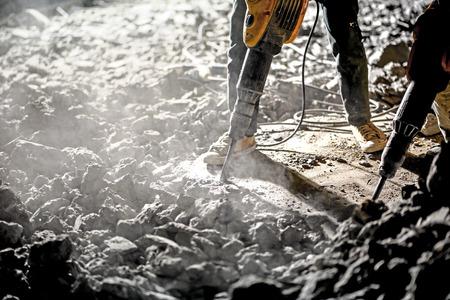 手持ち削岩機と夜に働く道路を修復します。