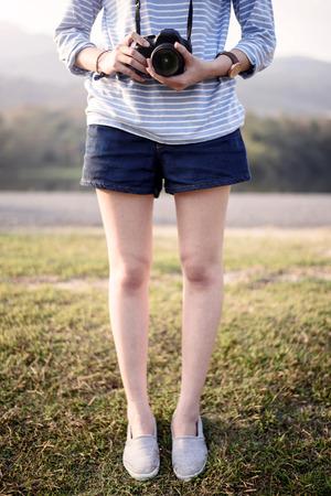 Hipster girl holds camera in garden