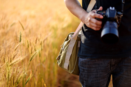 Photographer holding camera on wheat fields in warm sunset Foto de archivo