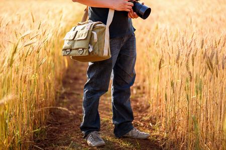 暖かい夕日の小麦畑にカメラを保持している写真家