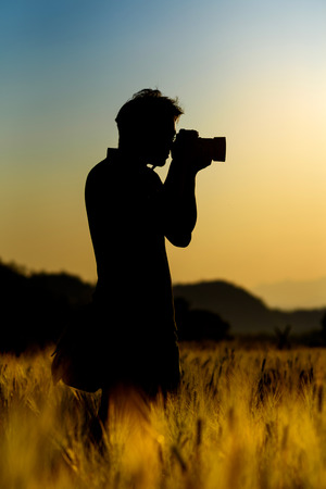 Silhouette of photographer during in sunset. Stock Photo