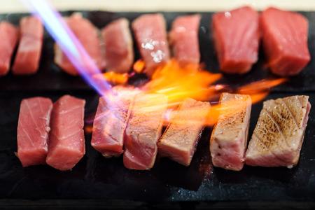 chef using a torch burn on tuna sashimi Stockfoto
