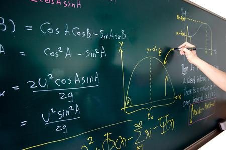 Closeup of hand writing complicated math equation on black board. 스톡 콘텐츠