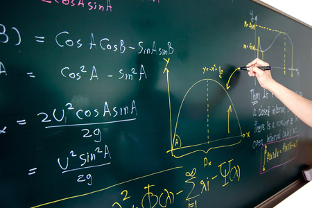 Closeup of hand writing complicated math equation on black board. Stockfoto