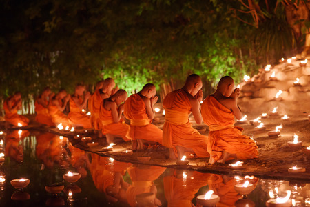 buddhism prayer belief: monks sitting meditate with many candle in Thai temple at night , Chiangmai ,Thailand, soft focus Stock Photo