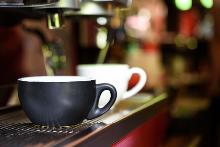 automat: Close-up of espresso pouring from coffee machine. Professional coffee brewing Stock Photo