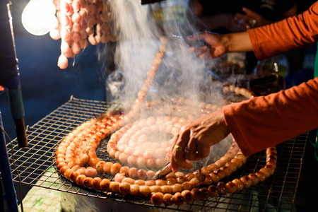 cooked pepper ball: Thai style sausage grilling on stove at night market Stock Photo