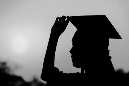 diploma: Silueta de la mujer graduada en la puesta del sol, blanco y negro Foto de archivo