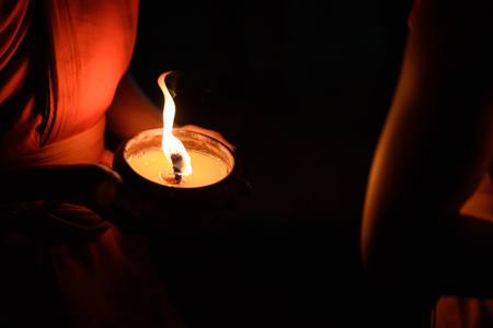 buddhism prayer belief: Buddhist monk hands holding candle cup in the dark ,Chiang mai , Thailand Stock Photo