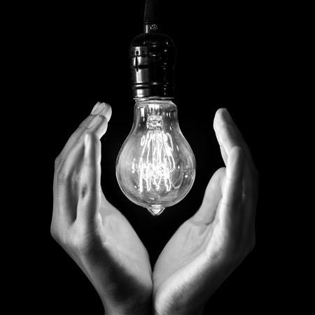 lightbulb hold in hand on black background , black and white Stock Photo