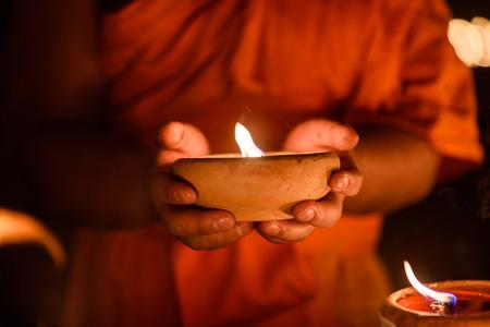 moine: les mains des moines bouddhistes tenant tasse bougie dans l'obscurité, Chiang Mai, Thaïlande