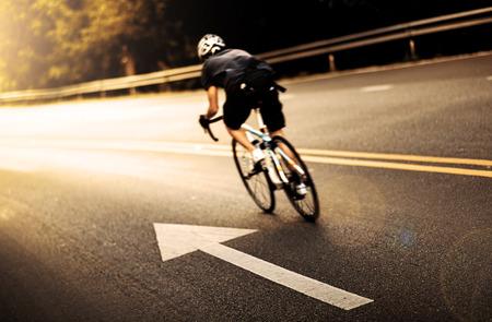 男性の山の朝の自転車道をサイクリング