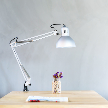Wooden Desk with Lamp in front of concrete wall in modern office