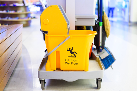 mopped: Yellow mop bucket and set of cleaning equipment department store