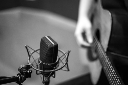 selective focus microphone and blur Man playing guitar background