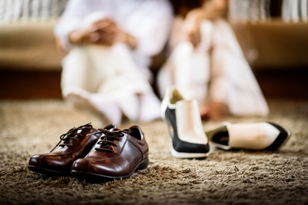 Wedding groom and bride shoes with married couple on luxury bed background