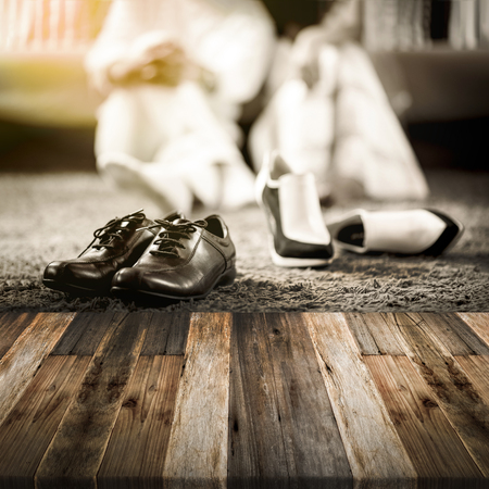 Wedding groom and bride shoes with married couple on luxury bed background with wooden floor Stock Photo