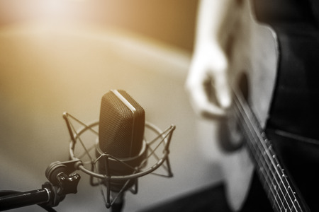 selective focus microphone and blur Man playing guitar background with flare light , vintage style